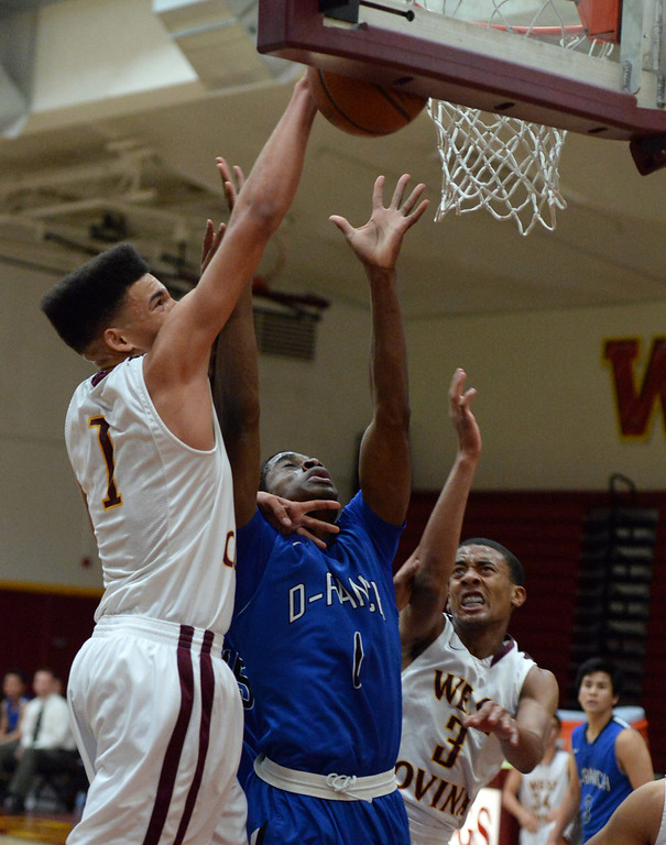 . West Covina\'s Michael Fallon (1) rebounds over Diamond Ranch\'s Ernest Ugoagu (1) in the first half of a prep basketball game at West Covina High School in West Covina, Calif., on Wednesday, Jan. 8, 2014. (Keith Birmingham Pasadena Star-News)