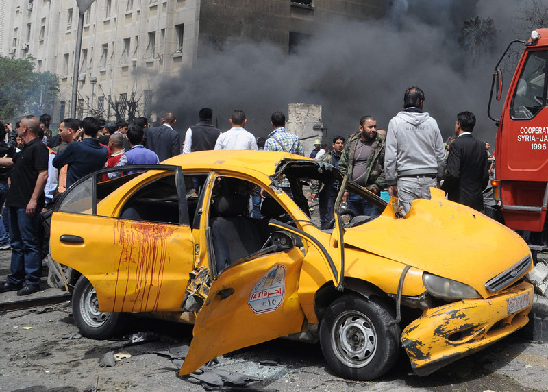 . This photo released by the Syrian official news agency SANA, shows Syrians inspecting a damaged car at the scene of a car bomb attack near the Sabaa Bahrat Square, one of the capital\'s biggest roundabouts, in Damascus, Syria, Monday, April. 8, 2013. A car bomb rocked a busy residential and commercial district in central Damascus on Monday, killing more than a dozen with many more injured and sending a huge cloud of black smoke billowing over the capitalís skyline, Syrian state-run media said. (AP Photo/SANA)