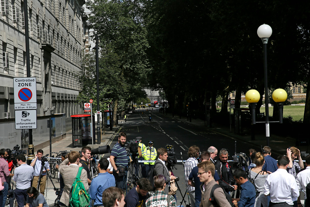 . Media and the public are kept far from the scene near of a car that crashed into security barriers outside the Houses of Parliament to the right of a bus in London, Tuesday, Aug. 14, 2018. Authorities said in a statement Tuesday that a man in his 20s was arrested on suspicion of terrorist offenses after a silver Ford Fiesta collided with a number of cyclists and pedestrians before crashing into the barriers during the morning rush hour. (AP Photo/Tim Ireland)