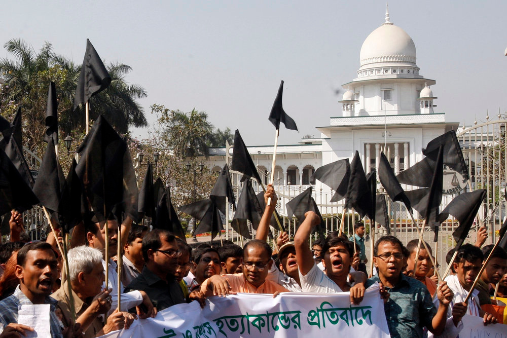 . Bangladeshi Hindus wave black flags as they march through a street to protest against alleged attacks by Jamaat-e-Islami activists in Dhaka, Bangladesh, Saturday, March 2, 2013. Rioting broke out in Bangladesh on Thursday after a war crimes tribunal gave a death sentence to Delwar Hossain Sayedee, a Jamaat-e-Islami leader, for atrocities linked to the country\'s 1971 independence war. A banner held by the protestestors reads: \'Protest against attacks.\' (AP Photo/Pavel Rahman)