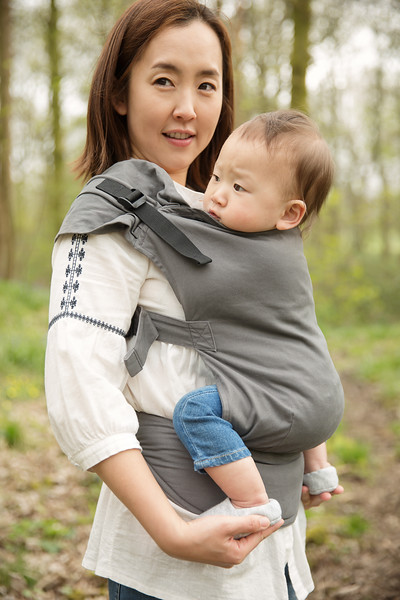 Izmi_Toddler_Carrier_Cotton_Mid_Grey_Lifestyle_Front_Carry_Side_View_Mum_Holding_Feet.jpg