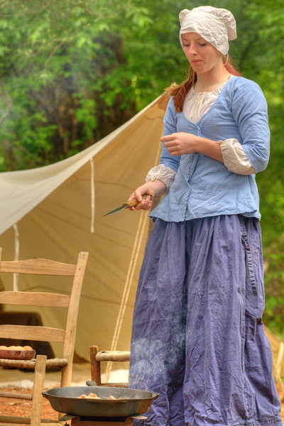 A woman prepares a meal in her camp during the Siege of Fort Watauga at Sycamore Shoals State Park in Elizabethton, VA on Saturday, May 17, 2014. Copyright 2014 Jason Barnette  The Siege of Fort Watauga is a two-day reenactment held each year at the recreation of the fort inside Sycamore Shoals State Historic Park. The reenactment brings in dozens of reenactors and hundreds of visitors as they tell the story of an attack on the early settlers village by Dragging Canoe, and how they successfully defended themselves. During the reenactment, the fort is open to the public with demonstrations of all areas of early settler life on the frontiers.