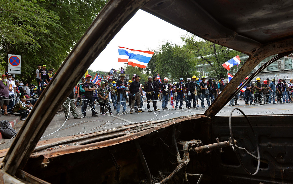 . A vehicle burnt during earlier clashes lies in the foreground as anti-government protestors wave Thai flags during a stand-off with Thai police near Government House in Bangkok on February 18, 2014.   AFP PHOTO / Manjunath Kiran/AFP/Getty Images
