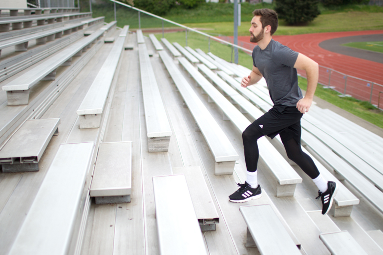 guy running bleacher stairs