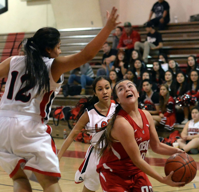 . Workman\'s Alicia Aguirre (00) drives to the basket past Gladstone\'s Erika Sanchez (12) in the first half of a prep basketball game at Gladstone High School in Covina, Calif., on Friday, Jan. 17, 2014. (Keith Birmingham Pasadena Star-News)