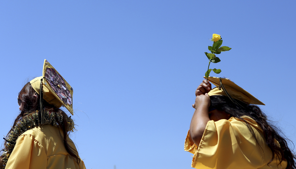 . Graduates carry yellow roses as the approach the stage at Watsonville High on Friday during the 2013 graduation ceremony. (Kevin Johnson/Sentinel)