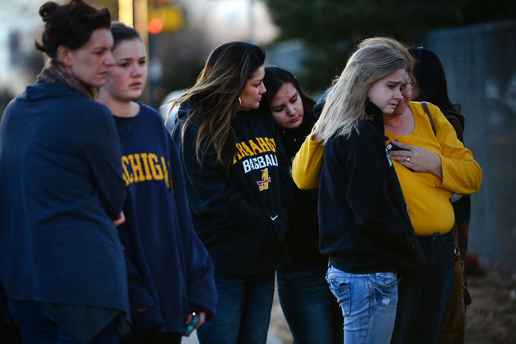 . Arapahoe High School senior Melissa Tombaugh, 18,  gets comforted by her mother Jeannette, right at a tribute set up to pray for shooting victim Claire Davis along Dry Creek road near Arapahoe High School in Centennial, CO on December 15, 2013. Students from the high school attended a prayer service to pray for the recovery of Davis who was shot during the recent shooting at the high school.  (Photo By Helen H. Richardson/ The Denver Post)