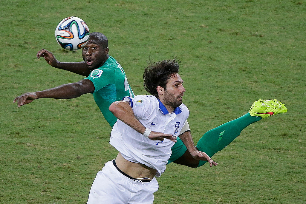 . Ivory Coast\'s Sol Bamba, left, and Greece\'s Giorgos Samaras battle for the ball during the group C World Cup soccer match between Greece and Ivory Coast at the Arena Castelao in Fortaleza, Brazil, Tuesday, June 24, 2014. (AP Photo/Sergei Grits)