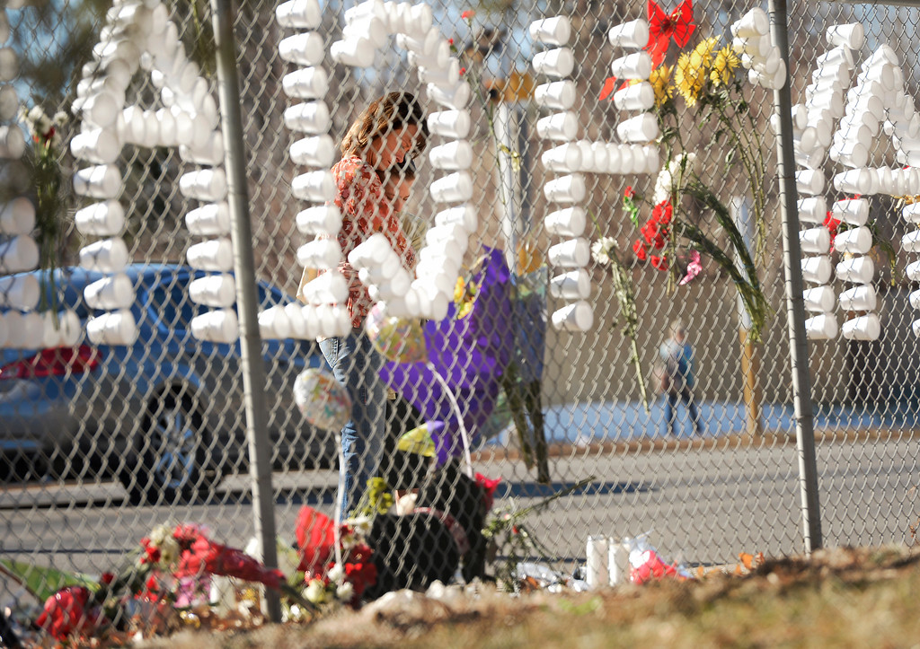 . Nicki Winingham and her son Logan, 14, a freshman at Arapahoe High School, pray together at a tribute on a fence near the school in Centennial, December 16, 2013. The school was the scene of a shooting on Friday that left a student gunman dead and two other students injured. (Photo by RJ Sangosti/The Denver Post)