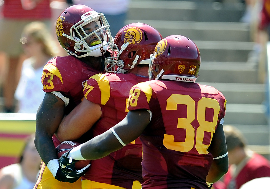 . Southern California running back Tre Madden (23) reacts with teammate offensive tackle Kevin Graf (77) and fullback Jahleel Pinner (38) after catching a 5 yard touchdown pass against Boston College during the first half of an NCAA college football game in the Los Angeles Memorial Coliseum in Los Angeles, on Saturday, Sept. 14, 2013.