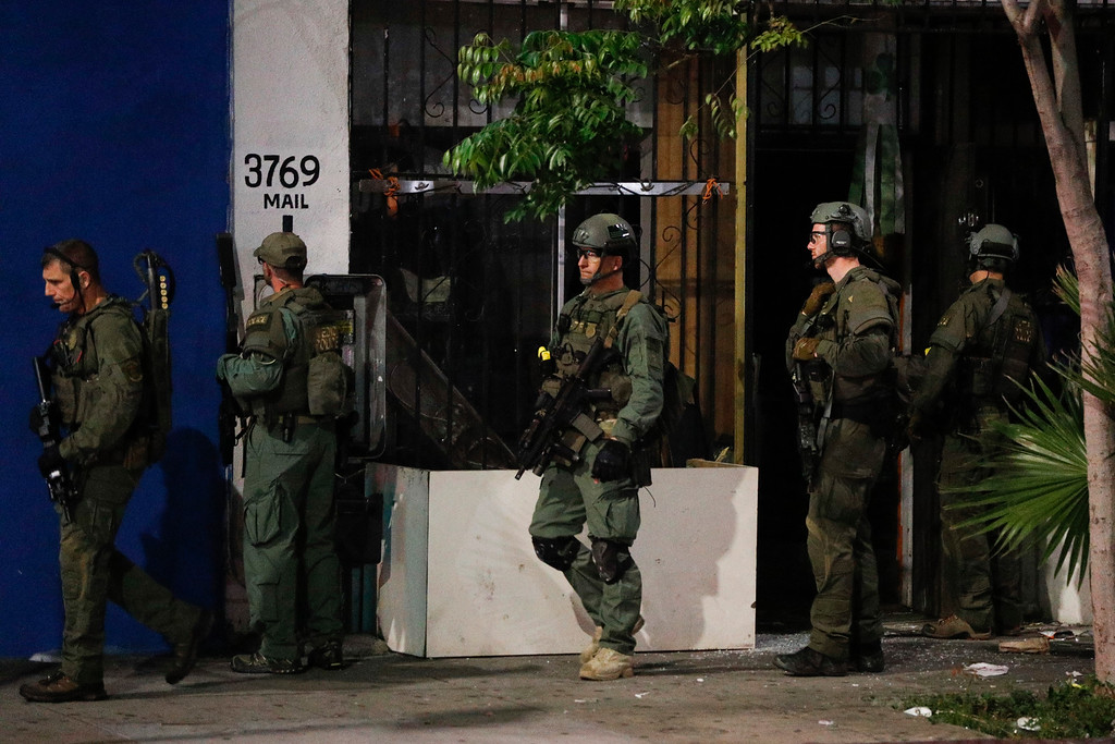 . ATF agents walk out of a store after conducting a raid Wednesday, May 17, 2017, in Los Angeles. Hundreds of federal and local law enforcement fanned out across Los Angeles, serving arrest and search warrants as part of a three-year investigation into the violent and brutal street gang MS-13. (AP Photo/Jae C. Hong)