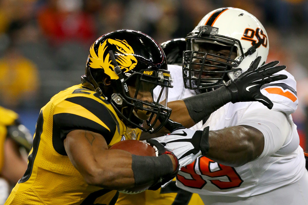 . ARLINGTON, TX - JANUARY 03:  Running back Henry Josey #20 of the Missouri Tigers runs against Calvin Barnett #99 of the Oklahoma State Cowboys in the first half during the AT&T Cotton Bowl on January 3, 2014 in Arlington, Texas.  (Photo by Ronald Martinez/Getty Images)