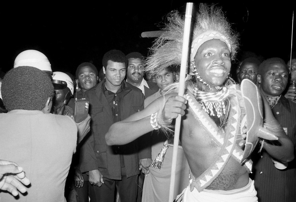 . Zaire dancer with spear moves ahead of Muhammad Ali through welcoming crowded at Kinshasa airport, September 10, 1974.     Ali arrived in a chartered Air Zaire plane from Paris for the world championship fight with George Foreman.   AP Photo/ Horst Faas)