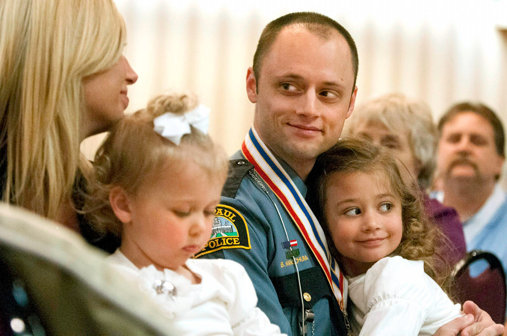 . St. Paul Police officer Brian Wanschura looks at his wife, Dana, after he received the Medal of Valor and Officer of the Year award. He shared the awards with his partner, Dan King. With Wanschura are his daughters Ella, 5, right, and Whitney, 2. (Pioneer Press: Chris Polydoroff)