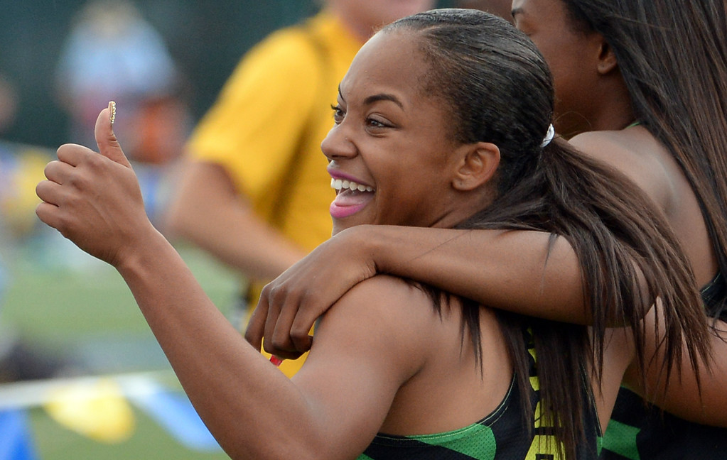 . Long Beach Poly\'s Jade Lewis, left, gives the thumbs-up as she hugs teammate Arianna Washington after Washington won the division 1 100 meter dash during the CIF Southern Section track and final Championships at Cerritos College in Norwalk, Calif., Saturday, May 24, 2014.   (Keith Birmingham/Pasadena Star-News)