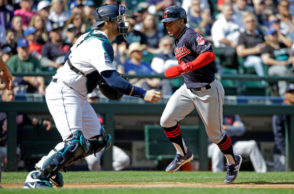 . Cleveland Indians\' Francisco Lindor, right, scores as Seattle Mariners catcher Mike Zunino waits for the ball in the third inning of a baseball game Saturday, Sept. 23, 2017, in Seattle. (AP Photo/Elaine Thompson)