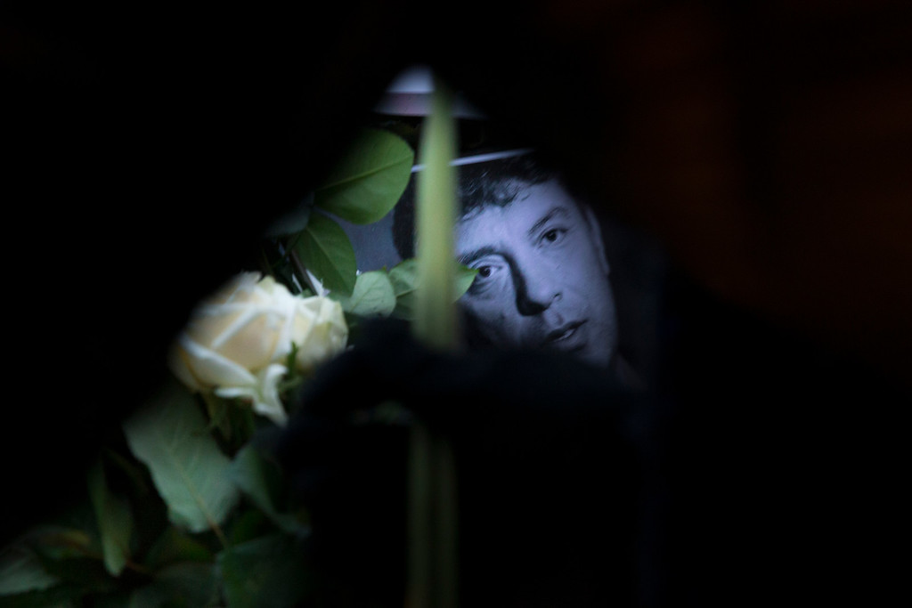 . Flowers and a portrait of Boris Nemtsov, a charismatic Russian opposition leader and sharp critic of President Vladimir Putin, was gunned down on Friday, Feb. 27, 2015 near the Kremlin, with St, Basil Cathedral is in the background in Moscow, Russia, Sunday, March 1, 2015. Thousands converged Sunday in central Moscow to mourn veteran liberal politician Boris Nemtsov, whose killing on the streets of the capital has shaken Russiaís beleaguered opposition. They carried flowers, portraits and white signs that said ìI am not afraid.î  (AP Photo/Pavel Golovkin)