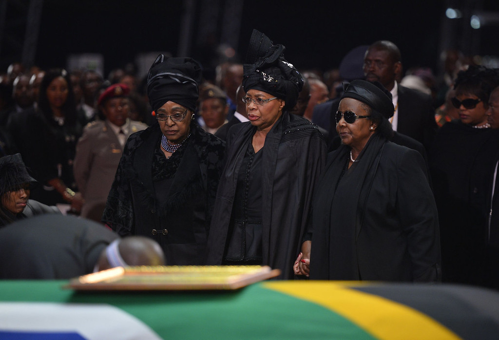 . The ex-wife of Nelson Mandela, Winnie Mandela Madikizela (L), and the widow of Nelson Mandela, Graca Machel (C), stand by the coffin of South African former president Nelson Mandela during his funeral ceremony in Qunu on December 15, 2013. Mandela, the revered icon of the anti-apartheid struggle in South Africa and one of the towering political figures of the 20th century, died in Johannesburg on December 5 at age 95.  AFP PHOTO / POOL / ODD ANDERSENODD ANDERSEN/AFP/Getty Images
