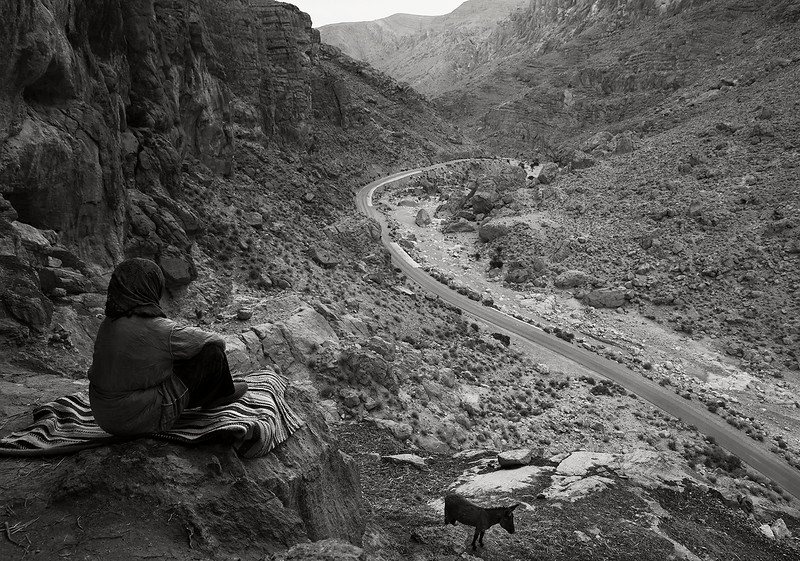A nomad woman sits outside her cave home and takes in the view.  Todra Gorge, Morocco, 2018