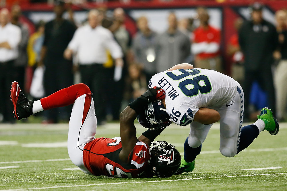 . Stephen Nicholas #54 of the Atlanta Falcons tackles  Zach Miller #86 of the Seattle Seahawks in the second quarter of the NFC Divisional Playoff Game at Georgia Dome on January 13, 2013 in Atlanta, Georgia.  (Photo by Kevin C. Cox/Getty Images)