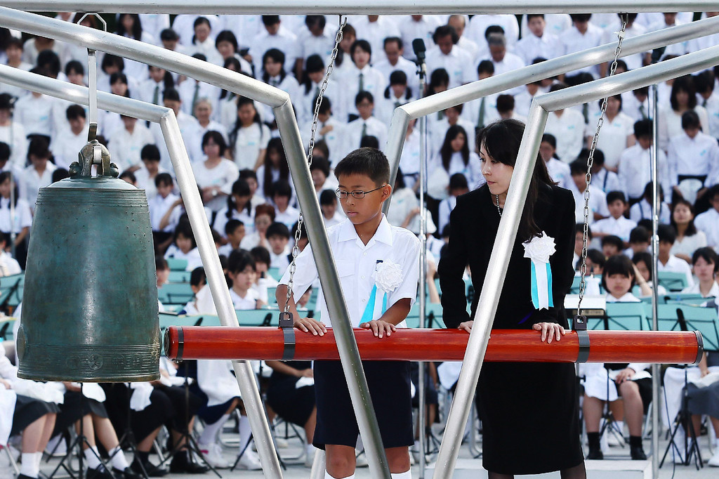 . Family members of atomic bomb victims strike the Peace Bell at a memorial service for A-bomb victims at the Peace Memorial Park in Hiroshima, western Japan on August 6, 2013 as ceremonies are held to mark the 68th anniversary of the bombing. AFP PHOTO / JIJI  PRESS/AFP/Getty Images