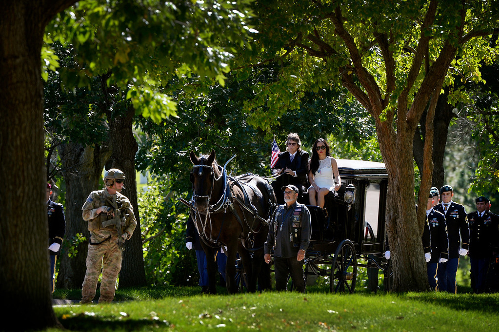 . DENVER, CO. - OCTOBER 02: Julie Huynh, right, rides with Lorraine Melgosa on a horse-drawn hearse carrying her fiance, Colorado National Guard Special Forces Soldier Liam Nevins at Fort Logan National Cemetery in Denver,CO October 02, 2013. (Photo By Craig F. Walker / The Denver Post)