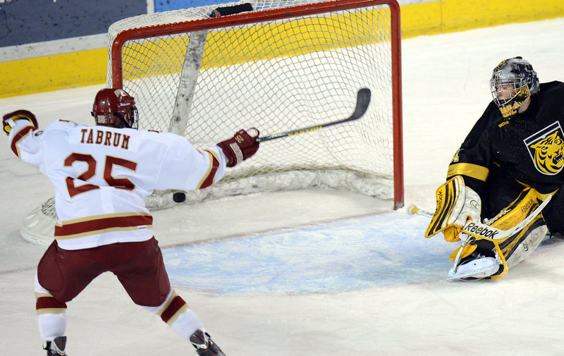 . DENVER, CO. - FEBRUARY 08: Matt Tabrum of University of Denver #25, left, celebrates his teammate Larkin Jacobson\'s goal on Joe Howe of Colorado College #31, right, in the 1st period of the game February 8, 2013 at Magness Arena in Denver, Colorado. (Photo By Hyoung Chang/The Denver Post)