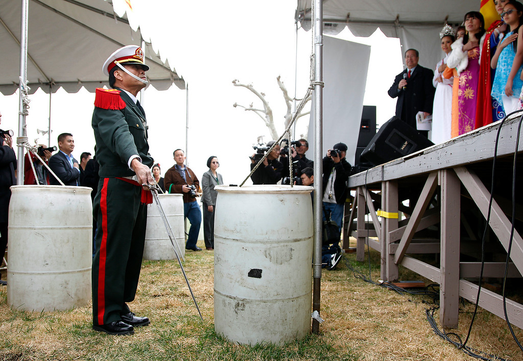 . At left, Hung Lai, General Secretary of the Coalition of Nationalist Vietnamese Organizations of Northern California (CONVONCA) stands at attention during the praying ceremony at the Tet festival hosted by CONVONCA at the Santa Clara County Fairgrounds in San Jose, Calif. on Saturday, February 2, 2013. Lai wears a uniform from when he attended the Vietnamese National Military Academy in 1967. (LiPo Ching/Staff)