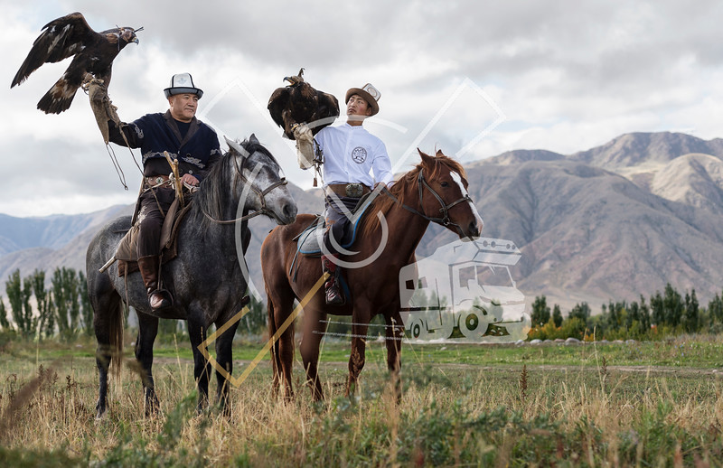 Kyrgyz men on a horse posing with their hunting eagles outdoors in Kyrgyzstan.