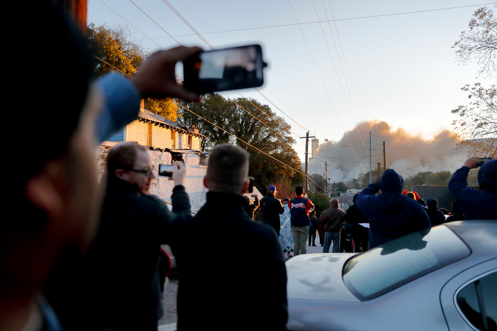 . A crowd watches as the Georgia Dome is imploded in Atlanta, Monday, Nov. 20, 2017. The dome was not only the former home of the Atlanta Falcons but also the site of two Super Bowls, 1996 Olympics Games events and NCAA basketball tournaments among other major events. (AP Photo/David Goldman)