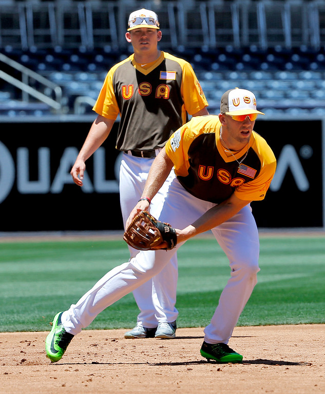 . U.S. Team\'s Hunter Dozier, of the Kansas City Royals, fields the ball as Ryon Healy, of the Oakland Athletics looks on prior to the All-Star Futures baseball game against the World team, Sunday, July 10, 2016, in San Diego. (AP Photo/Lenny Ignelzi)