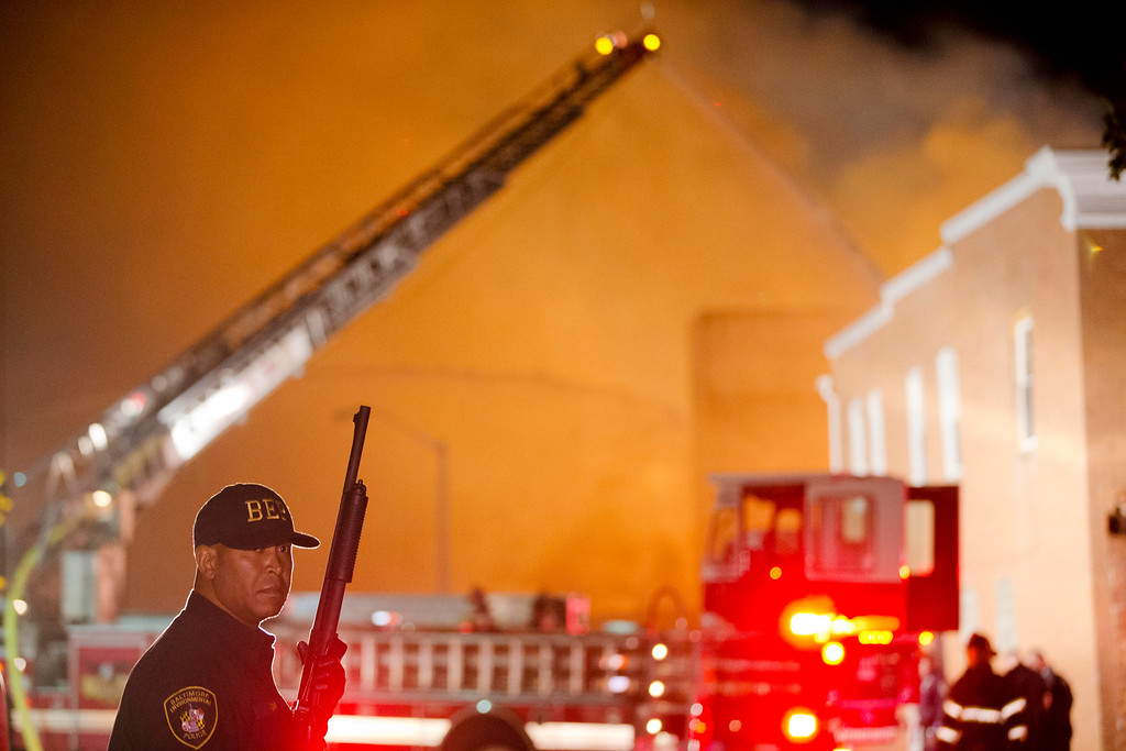 . A law enforcement officer stands guard as firefighters battle a blaze, Monday, April 27, 2015, after rioters plunged part of Baltimore into chaos, torching a pharmacy, setting police cars ablaze and throwing bricks at officers. (AP Photo/Matt Rourke)