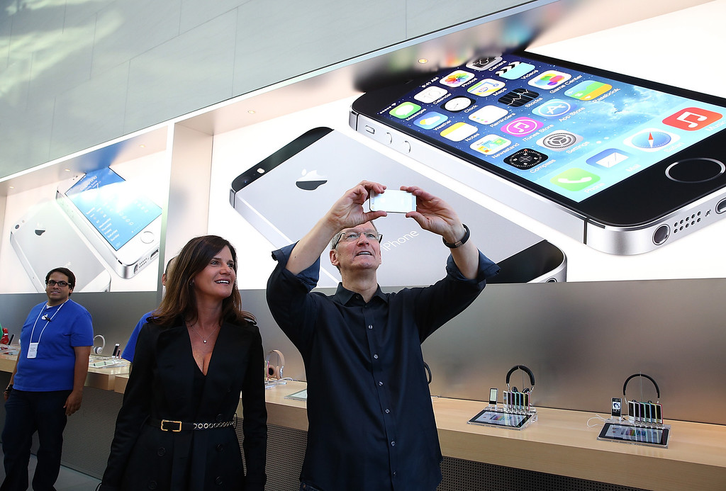 . Katie Cotton, Apple vice president of corporate communications (L) looks on as Apple CEO Tim Cook (R) uses an iPhone to take a picture of customers waiting in front of an Apple store to purchase the new iPhones on September 20, 2013 in Palo Alto, California. Apple launched two new models of iPhone: the iPhone 5S, which is preceded by the iPhone 5, and a cheaper, paired down version, the iPhone 5C. The phones come with a new operating system.  (Photo by Justin Sullivan/Getty Images)