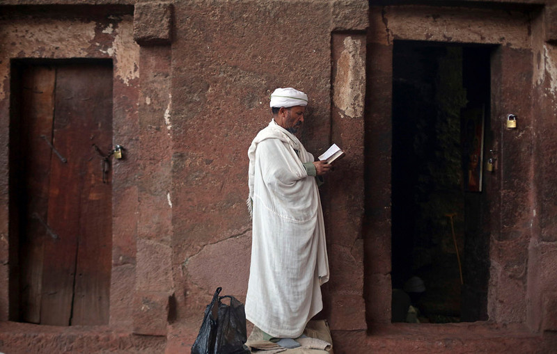. An Orthodox Christian prays in front of one of the 11 monolithic rock-cut churches ahead of Orthodox Easter in Lalibela May 4, 2013. The main religious mass takes place on Saturday night, a sombre, sacred occasion with music and dancing until the early hours of the morning. At midnight a chicken is slaughtered for symbolic reasons. According to legend, angels helped King Lalibela build this church and others like it in the 11th and 12th century after he received an order from God to create a new Jerusalem in Ethiopia. Picture taken May 4, 2013. REUTERS/Goran Tomasevic
