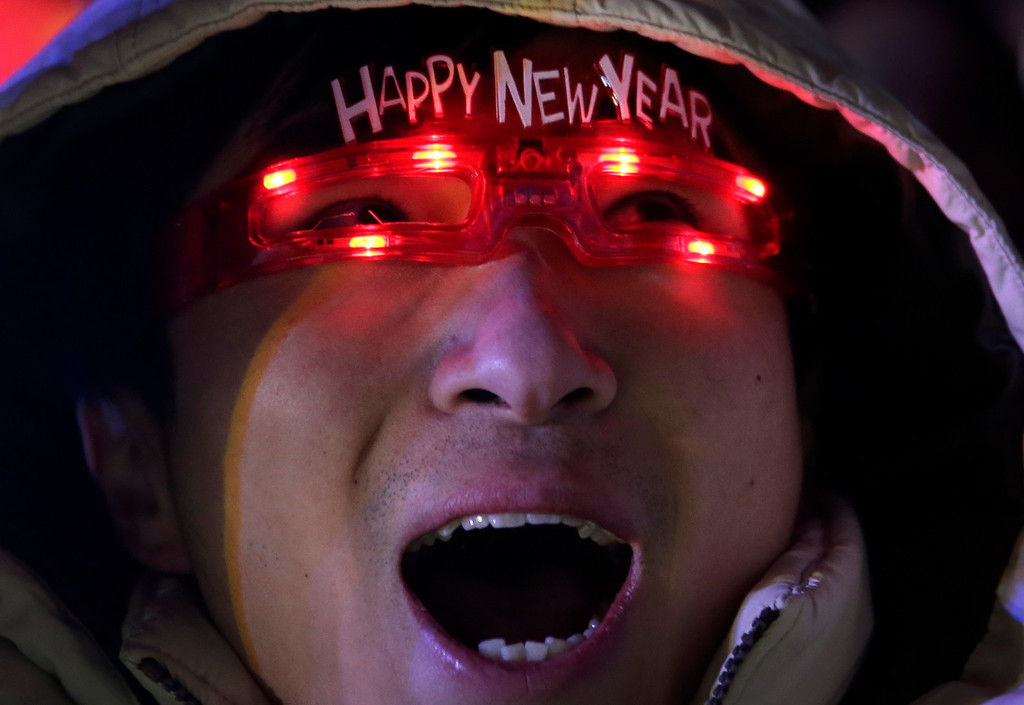 . A Chinese man wearing illuminated glasses celebrates the New Year during a count-down event in front of the National Stadium in Beijing, China Thursday, Jan. 1, 2015. Organizers showcase Beijing\'s 2022 Winter Olympics bid to kick off the new year. (AP Photo/Andy Wong)