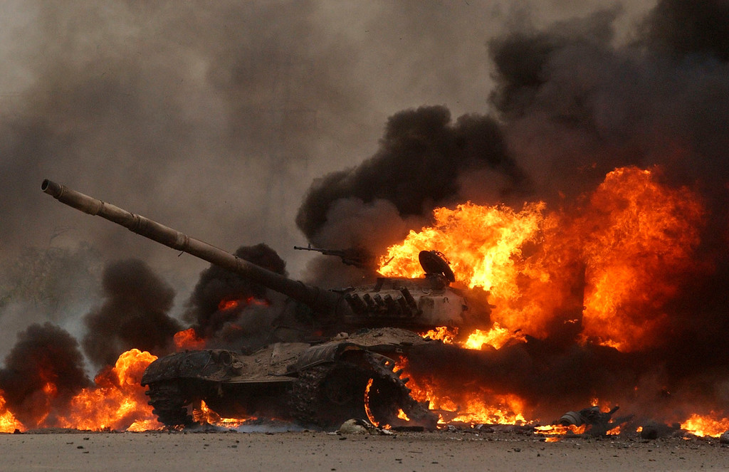 . An Iraqi T72 tank erupts in flames after 2nd Tanks Battalion Bravo Company blew it up on their way to a blocking position near the Tigris River on the outskirts of Saddam City, near the Tigris River. The tank had no personnel but was full of fuel and ammunition. The combat train took fire from an ambush with the enemy firing AK-47\'s from both sides of the narrow road while driving through a small city. The Marines from the 1st, 5th and 7th Regimental Combat Teams, headed for Saddam City for their objective. (Andy Cross, The Denver Post)