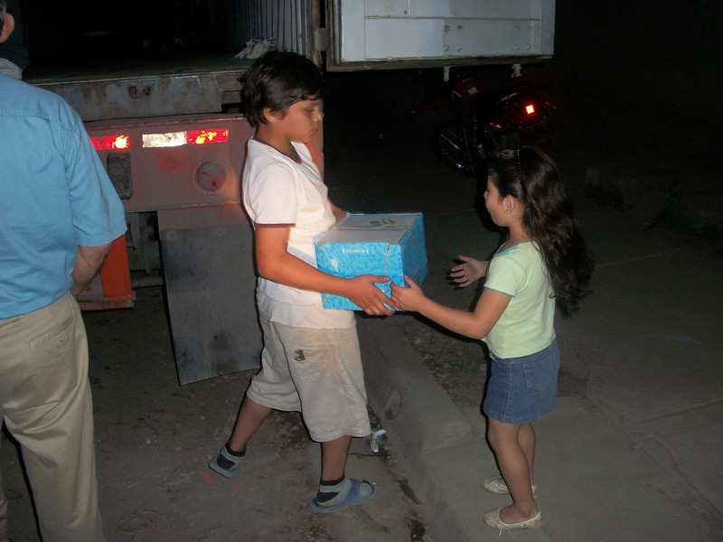 Two kids from the neighborhood came to watch and a short time later asked if they could help. he work was hard  but there was lots of laughing and everyone enjoyed themselves.  Our two young workers were rewarded for their initiative with a box and we were rewarded with a big big smile.