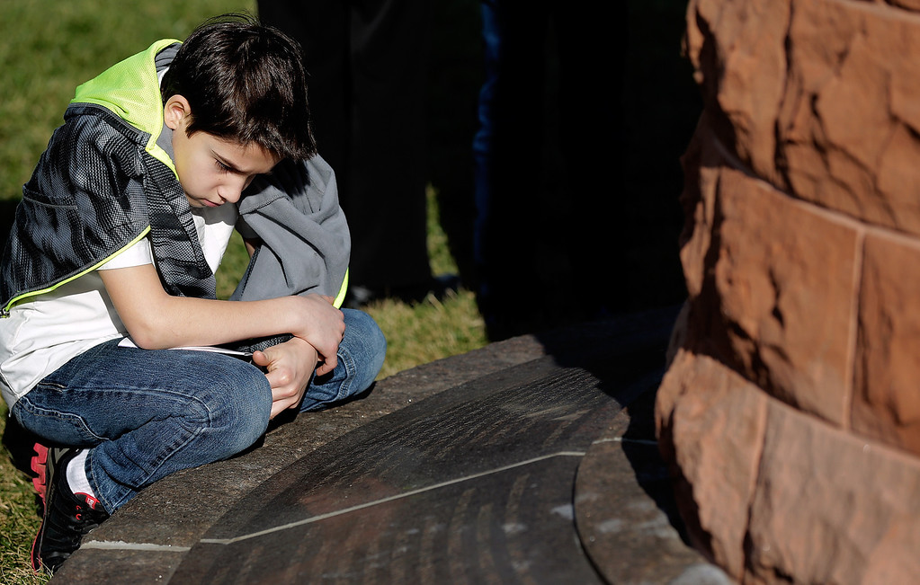 . Family members search for the names of loved ones carved into the base of a cairn during a remembrance ceremony for those who died on Pan Am Flight 103 at Arlington National Cemetery December 21, 2013 in Arlington, Virginia.  (Photo by Win McNamee/Getty Images)
