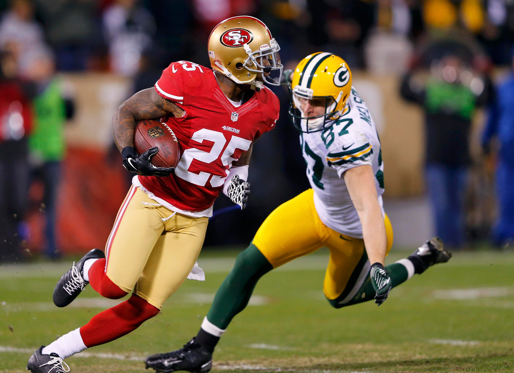 Description of . San Francisco 49ers Tarrell Brown (L) runs past Green Bay Packers Jordy Nelson after intercepting a pass in the second quarter during their NFL NFC Divisional playoff football game in San Francisco, California, January 12, 2013.  REUTERS/Mike Blake