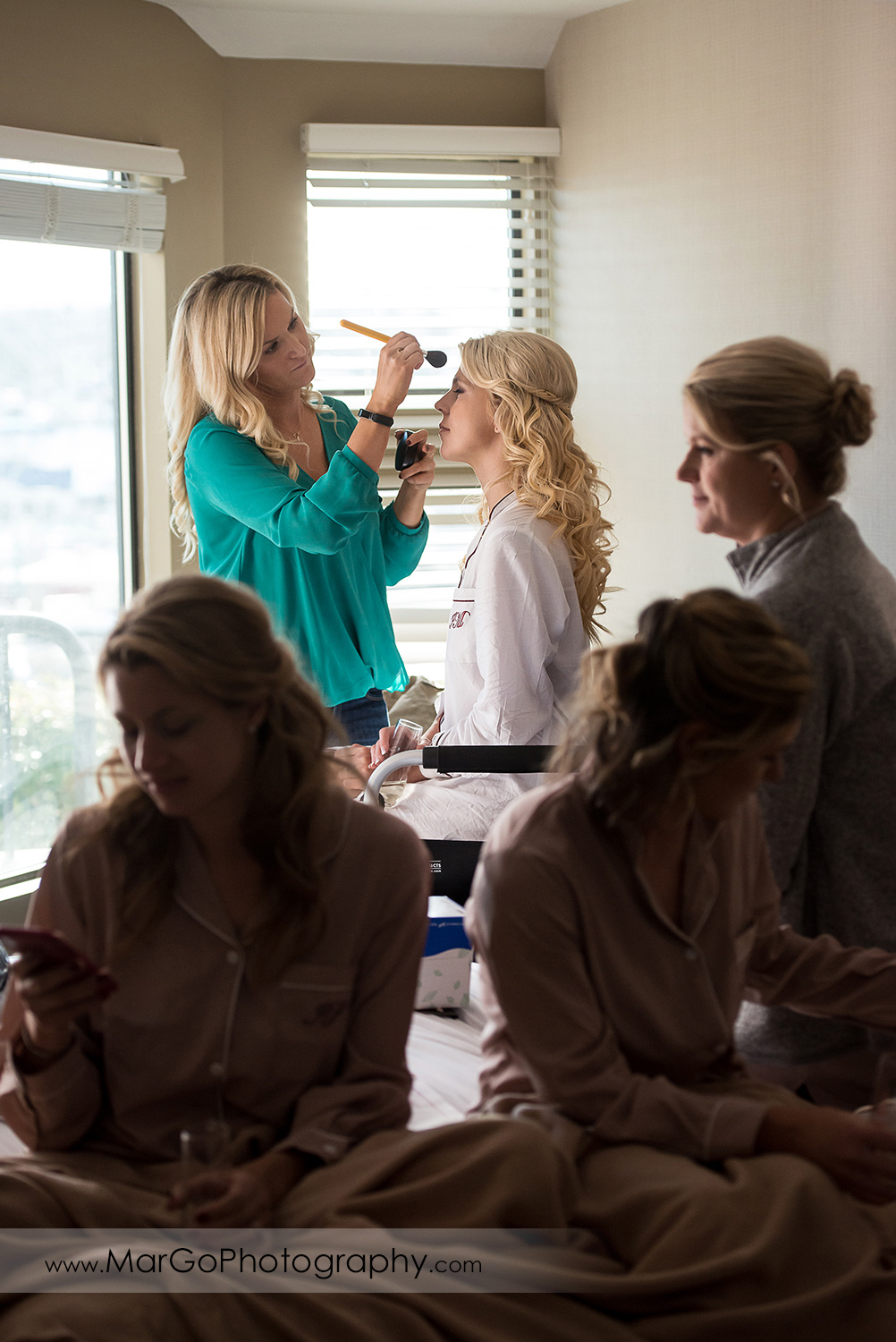 bridal make-up with bridesmaids in foreground at San Diego Hyatt Regency Mission Bay Hotel