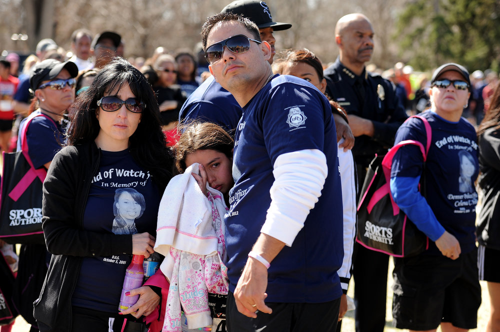 . As the doves were released family and friends remember their fallen comrade. DPD officer Rick Beall hugs his daughter Alexis, 11 and wife Tiffinny, left.  Family, colleagues, and friends of slain Denver Police Officer Celena Hollis turned out April 7, 2013 for a 5k run and walk to raise money for a scholarship fun and a memorial bench in City Park in Denver, CO.  Over 300 runners and walkers participated in the race that started at 9:00 am.  The race looped around City Park.  After the race, a gathering was held to remember Hollis and 22 white doves were released in her memory.  (Photo By Helen H. Richardson/ The Denver Post)