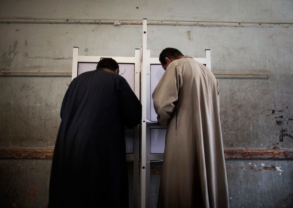 . Egyptian men fill their ballots at a polling station in the Coptic Mensheit Nasser district in Cairo on May 23, 2012, as Egyptians vote in historic presidential elections contested by Islamists and secularists promising different futures for the country after the overthrow of veteran dictator Hosni Mubarak. MARCO LONGARI/AFP/GettyImages