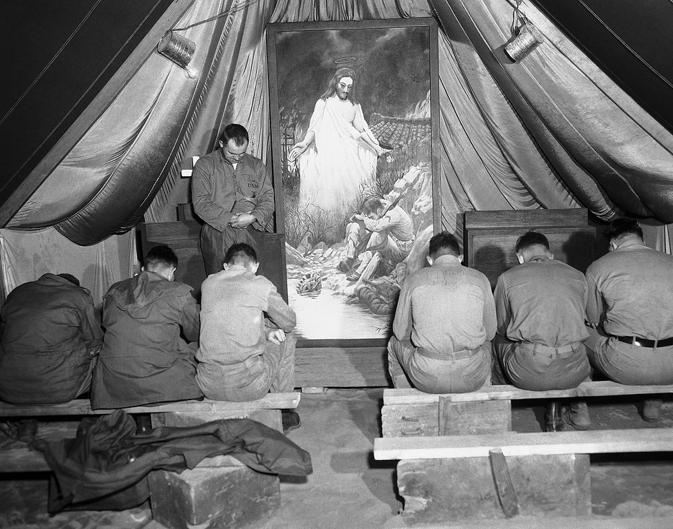 . A painting depicting Christ, The Prince of Peace, consoling a battle-weary Marine, provides an appropriate background in the Korean tent, Dec. 15, 1952 where Lt. Karl Ernst leads First Division leathernecks in prayer. The painting was executed by one of the marine in the outfit. Lt. Ernst, a Protestant navy chaplain, is from McLean, Texas. (AP Photo/FW)