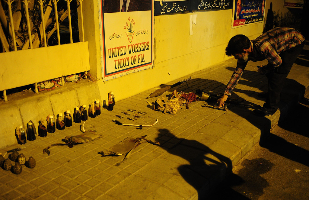 . A Pakistani security personnel arrange seized weapons after militants attacked Jinnah International Airport in Karachi on June 9, 2014. AFP PHOTO/Asif HASSAN/AFP/Getty Images