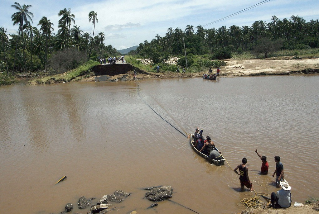 . People cross the river near a destroyed bridge in Coyuca de Benitez, Guerrero state, Mexico, after heavy rains hit the area on September 18, 2013.  AFP PHOTO/ Pedro  PARDO/AFP/Getty Images