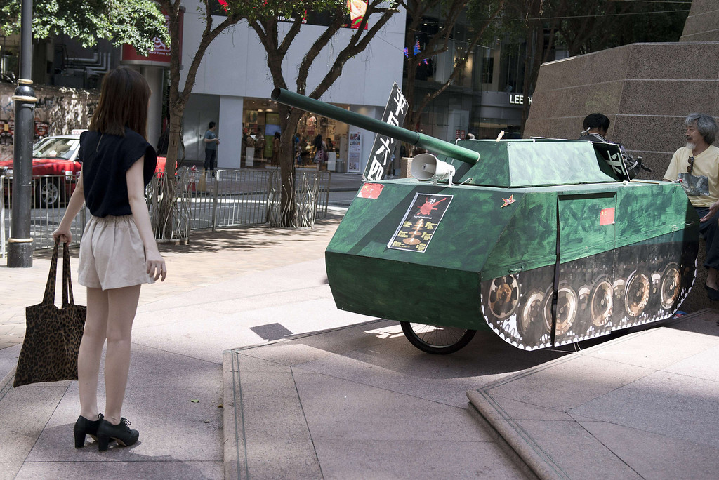 ". A young woman reenacts the famous ""Tank Man\"" scene from the 1989 Tiananmen Square military crackdown on pro-democracy protesters om Beijing, in front of a replica of a Chinese tank in Hong Kong on June 4, 2014. Up to 200,000 people were set to take part in a candlelight vigil in Hong Kong on June 4 to commemorate the 25th anniversary of the bloody Tiananmen Square crackdown, as China seeks to wipe the incident from memory.  AFP PHOTO / ALEX Ogle/AFP/Getty Images"