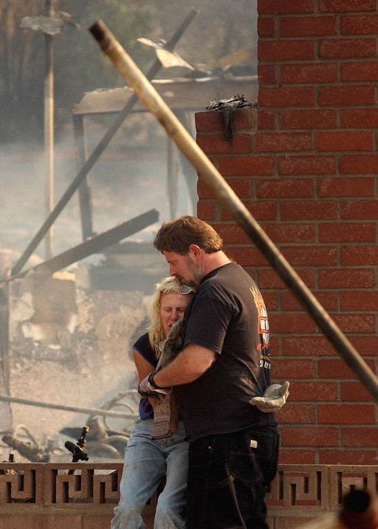 . Ten years ago this month the arson caused Old Fire, fanned by Santa Ana winds burned thousands of acres, destroyed hundreds of homes and caused six deaths. The fire burned homes in San Bernardino, Highland, Cedar Glen, Crestline, Running Springs and Lake Arrowhead and forced the evacuation of thousand of residents. Sam Goldstein hugs his wife Tami Goldstein after Tami is overcome while searching through the remains of their home at 1436 E. Ralston Avenue, in San Bernardino. The Goldstein\'s home was destroyed by the Old Fire. (Staff file photo/The Sun)
