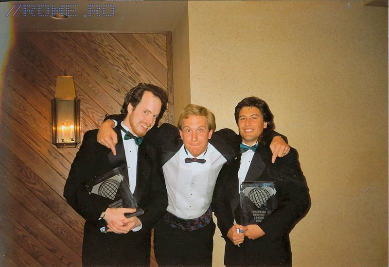 "Left to right: Tom Hall, Jay Wilbur, John Romero  This picture was taken just after the ""Summer Shareware Seminar"" Shareware Industry Awards in 1992. We got awards for two categories that both related to our second Commander Keen series (4-5) that we sold as shareware. Keen 6 (Aliens Ate My Baby Sitter!) was published in retail so it wasn't part of this award. We all rented tuxedoes for the event - something I've rarely done for award events since then! I'm writing this in 2004 and Jay Wilbur has been working at Epic Games for more years than he worked at id Software and Tom Hall is working with me at Midway Home Entertainment in San Diego - we've worked together for over 15 years!"