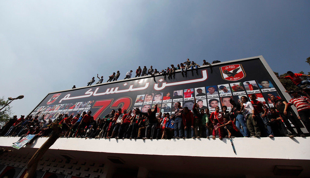 """. Al-Ahly fans, also known as \""""Ultras\"""", shout slogans against the Interior Ministry, in front of the Al-Ahly club after hearing the final verdict of the 2012 Port Said massacre in Cairo March 9, 2013.  The poster with pictures of fans who died in Port Said reads \""""We can\'t forget you\"""". REUTERS/Amr Abdallah Dalsh"""