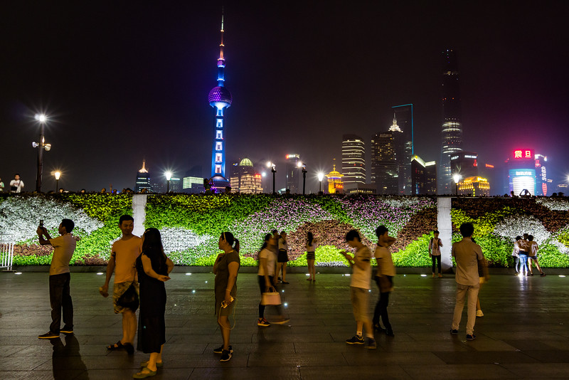 Residents and visitors enjoy a summer evening in central Shanghai near the Huangpu River